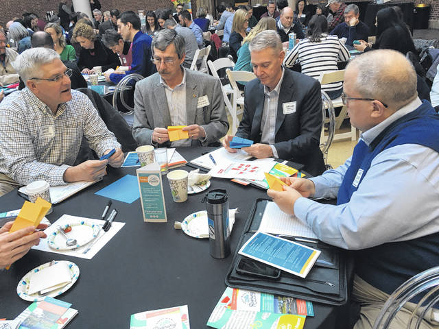 """Officials from Sidney attempt a """"hands on"""" exercise at the Great Miami Riverway Summit held at the Dayton Art Institute on Friday. They include, left to right, Parks and Recreation Director Duane Gaier, Councilmember Steve Wagner, Sidney Visitor's Bureau Director Jeff Raible and City Manager Mark Cundiff."""