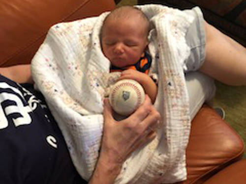 Chase Samuel Stammen, the newborn son of Versailles alumnus Craig Stammen and his wife Audrey, is pictured with the final ball his dad used to strikeout the side in the sixth inning of Thursday's exhibition game against Cleveland at Goodyear, Arizona. The San Diego Padres took and held the lead immediately after Stammen pitched, making him the winning pitcher.
