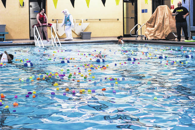 """The Easter Bunny watches as swimmers go for an Easter egg hunt Saturday in the pool at the Sidney-Shelby County YMCA. Hundreds of eggs were seen floating on the water as the swimmers """"found"""" them."""