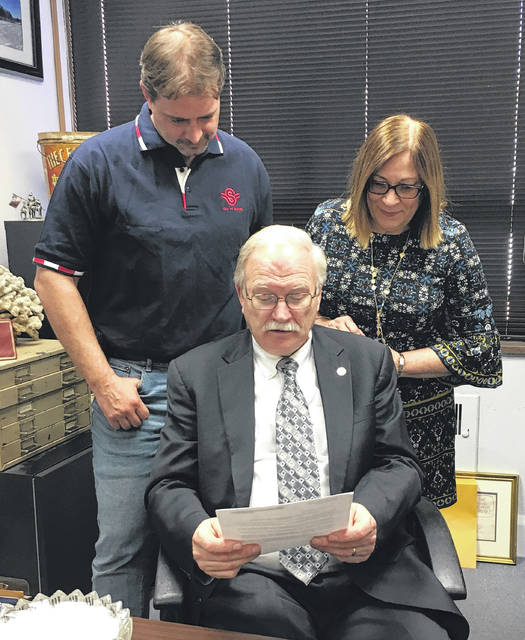 Sidney Arborists Brian Green, left, and Joyce Reier look over the letter that Mayor Mike Barhorst, center, recieved which informs the city that Sidney has again earned Tree City USA designation.