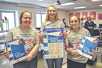 """Newton High School National Honor Society members Kacie Tackett, Paiton Miller and Halli Gipe wear the CBC """"Be The Red"""" high school blood drive T-shirt designed by Newton graduate Aliya Stine."""