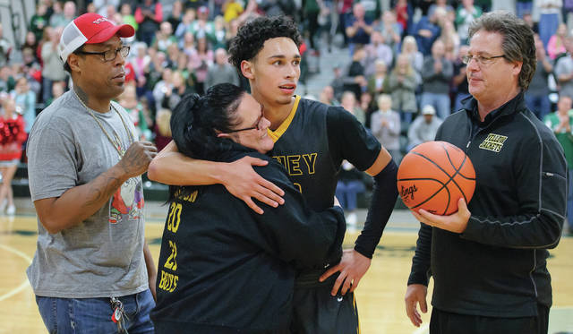 Sidney junior guard Andre Gordon hugs his mother Tracy Williams shortly after surpassing 1,000 career points in a game at Greenville last December. At left is Andre Gordon Sr., and at right is Sidney coach John Willoughby.