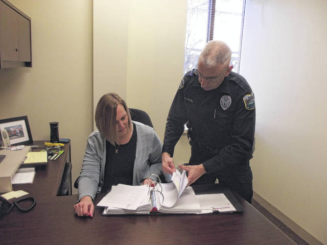 Sidney Police Officer Mike McRill and Becky Drinnen look over McRill's book which contains information about every person he's talked to who has a drug addiction.