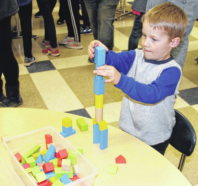 """Kindergartener Abe Counts, son of Rodney and Laura Counts, of Russia, builds a """"skyscraper"""" with blocks during STEM Night at Russia Local School."""
