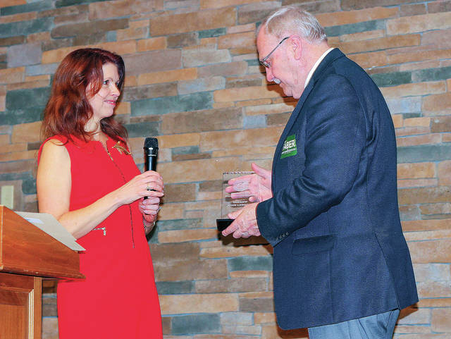 Shelby County Republican Central Committee Chairman Julie Ehemann, left, of Anna, presents Shelby County Sheriff John Lenhart, of Jackson Center, with the Republican of the Year award during the annual Lincold Day Dinner, Thursday, April 5, in Botkins.
