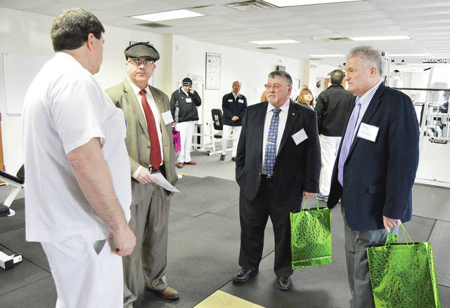 Darby Watkins, left to right, of Sidney, talks with city of Sidney Council member Joe Ratermann, and Shelby County Commissioners Bob Guilozet and Tony Bornhorst during a tour of the new NKP/HealthStat Care Clinic during a grand opening.