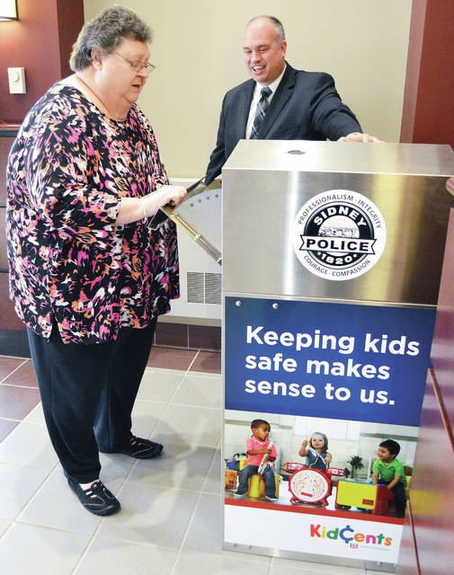 Eileen Wiseman, left, of Sidney, and Sidney Police Chief Will Balling check out the new drug drop-off box located in the Sidney Police Station.