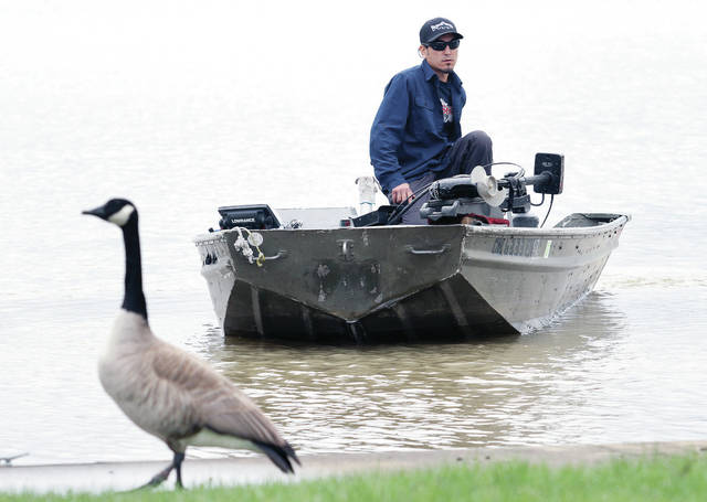 Royce Yamada, of Covington, takes his boat out onto Lake Loramie for the first time after patching damage to the boat caused when he encountered rapids on the Great Miami River while fishing. Yamada going out on the lake to see if the patches would hold. A wary goose with a damaged foot eyes Yamada on his test run.