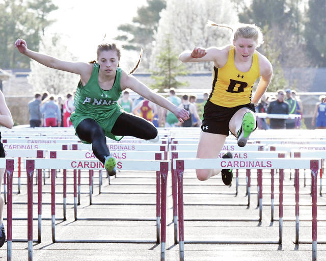 Anna's Hannah Shoemaker and Botkins' Adriana Jutte compete in the 100-meter hurdles on Friday during the New Bremen Cardinal Invitational.