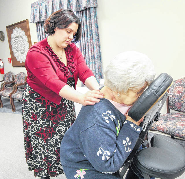 Leeann Stroud, of Wapakoneta, a massage therapist with Johnna in New Knoxville, gives Barb Seigle, of Sidney, a back massage during spa night at Ohio Living Dorothy Love Monday night.