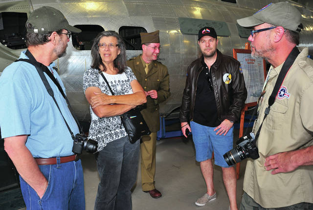 Mike Ullery | AIM Media Midwest Dan and, Janice Dana Ehrlich, along with Paul Bellamy, Andy Swinnen, and Greg Schafer, l-r, chat in front of B-17 <em>Champaign Lady</em> at Grimes Air Field on Monday during the first day of The Gather of B-17s event in Urbana. The Dana's father was a waist gunner in a B-17 during World War II. Bellamy, who is from England and Swinnen, who traveled from the Netherlands for the event, are both historians on the 401st Bomb Group, of which Champaign Lady was a part. Schafer is a volunteer for the Champaign Aviation Museum. The events of today lead up to the a reunion of the 401st Bomb Group later this week and the debut of the newly-restored B-17 <em>Memphis Belle</em> at the National Museum of the United States Air Force on Thursday.