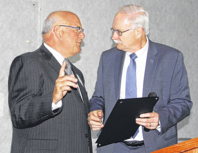 Former Sidney-Shelby Economic Partnership (SSEP) Executive Director Mike Dodds, left, is honored with a proclamation by Sidney Mayor Mike Barhorst at an open house at Shelby Oaks Golf Club, Thursday, May 10. Dodds retired from SSEP, May 11, after 11 years with the organization.