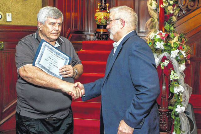 Mark Wahl, right, senior vice president of operations at Airstream in Jackson Center, congratulates 50-year employee Bob Sanford during Airstream's dinner to honor long-term employees recently at Greatstone Castle in Sidney.