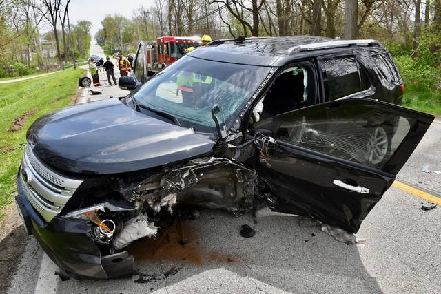 Port Jefferson firefighters, back left, huddle shortly after a two-vehicle crash in Pasco on Saturday. A black SUV and a white sedan were involved in an accident on state Route 29 near the Mosquito Creek bridge shortly before noon.