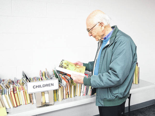 Dan Dickas, of Sidney, looks at the children's books at the Amos Memorial Library book sale Monday. The library has expanded the book sale into a week event and it will be held twice a year at the library. Hours for the sale are from 11 a.m. to 6 p.m. through Friday, May 4.