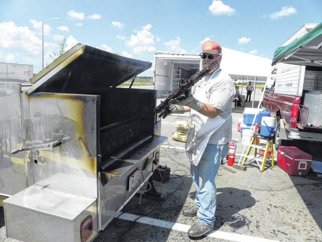 Dan Perverly, of Perverly Port-a-pit, of Edgington, Ohio, flips the chicken as it is cooking during the 2017 Council of Religious Education chicken and pork chop dinners. This year's event will be held Saturday, May 5, from 11 a.m. to 6:30 p.m. at the Menard's parking lot. Dinners are $8 each and include a choice of chicken or pork chops, potato chips, applesauce, butter and roll. The dinner is carry-out only and tickets may be purchased at the event. The Sidney Council of Religious Education is part of a national program that was started in 1921. Sidney elementary public school students come out of their school to a bus that the nondenominational Sidney Council of Religious Education teaches from.
