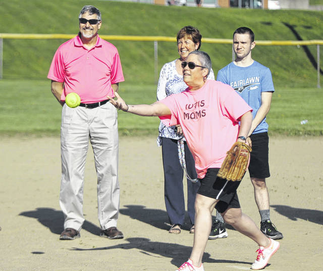 Alison Martin, of Sidney, throws out the first pitch of the IUTIS Club softball season Monday night. The season has been dedicated to the memory of Ty Austin Martin, son of Alison and Tim Martin, who died while serving with his church youth group in Mexico in 2016. A plaque and the softball were presented to Martin's family.