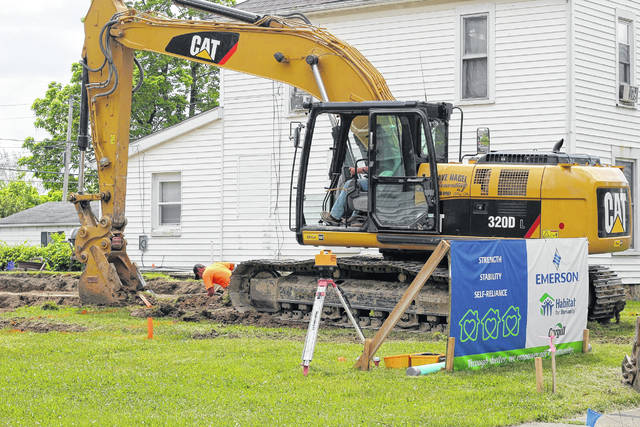 Ben Frantz, left in orange shirt, and Dave Nagel, in the backhoe, both of Dave Nagel Excavating LLC, break ground for the foundation of a house being constructed by Habitat for Humanity of Miami and Shelby Counties along Second Avenue in Sidney, Wednesday, May 31. Emerson Climate Technologies sponsors the build for Kelly Beemer and her children, of Sidney.