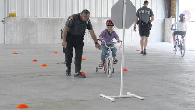 An officer helps a bicyclist learn the rules of riding her bicycle during a previous Bicycle Safety Day in Wapakoneta.