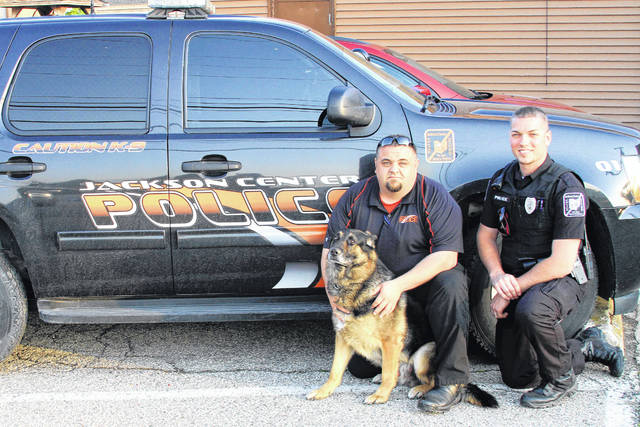 """Jackson Center Village Police Chief Chuck Wirick, left, and Deputy Zac Smith pose with Hero, the village's police dog. The police department is creating a fundraiser to help defray the costs associated with the canine unit and will be selling """"Hero"""" T-shirts at the upcoming Jackson Center Community Days Celebration."""