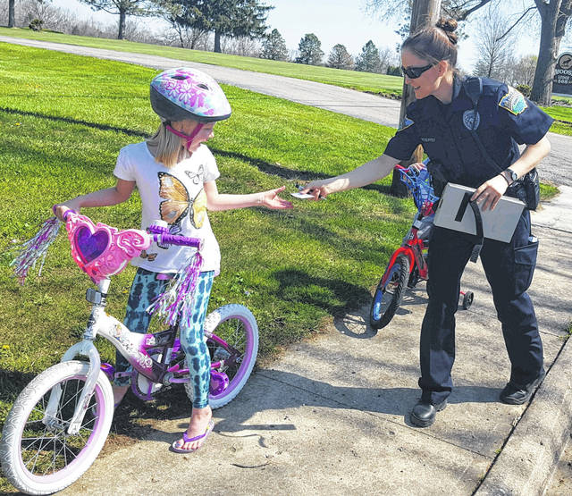 """Sidney Police Officer Rachel Croskrey gives a """"ticket"""" to Elyse, 6, of Sidney, for wearing a helmet while riding her bicycle. The """"ticket"""" is good for an ice cream cone at McDonalds."""