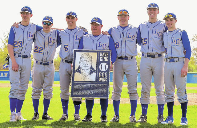 Lehman coach Dave King, center, poses with Lehman players shortly after being presented with a commemorative plaque prior to the team's game against Hardin Northern on Saturday. King surpassed 600 career wins on Thursday. A similar plaque will be installed at Lehman's baseball field.