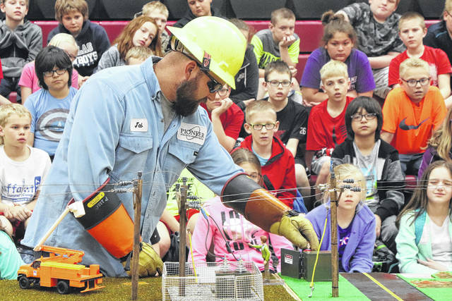 Pioneer Lineman Trainee Jeb Friend shows students what happens when various objects and equipment come in contact with power lines. Friend was presenting a program at Fort Loramie Elementary School.