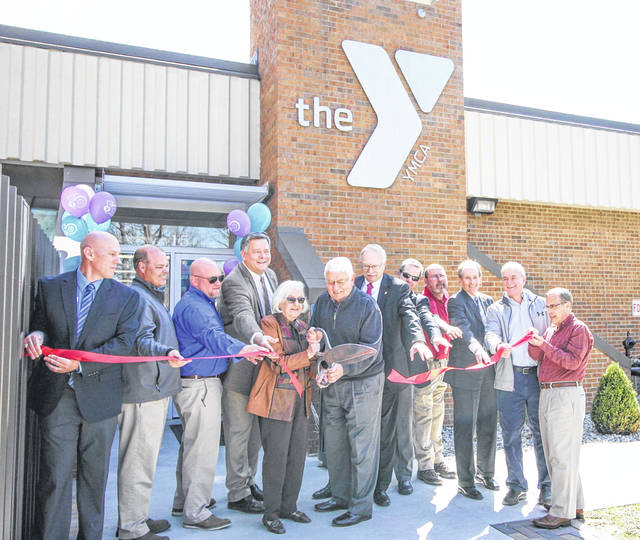 Sandy and Tom Shoemaker cut the ribbon to reopen the west entrance at the Sidney-Shelby County YMCA Monday morning.