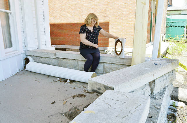 Shelby County Historical Society Director Tilda Phlipot looks at the metal base of a wood porch column lying at her feet. The column, along with the front wall of the porch of the Ross Historical Center in Sidney, was damaged when it was hit by a car during a crash, Saturday, April 28.
