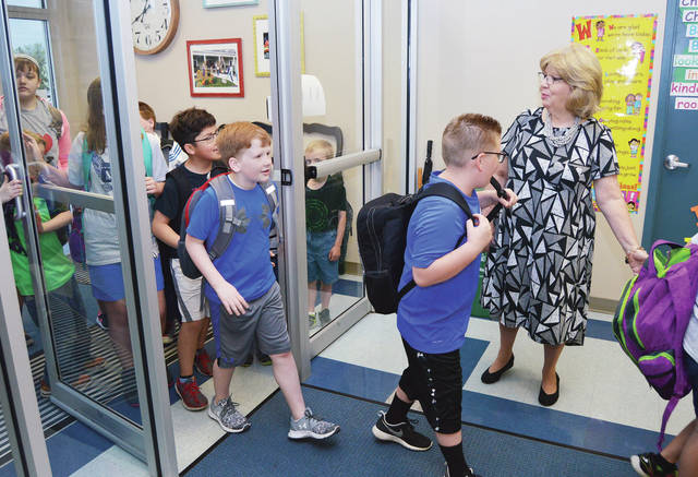 Christian Academy Schools Superintendent Mary Smith greets her students as they arrive at school Thursday, May 4. Smith is retiring at the end of the school year.
