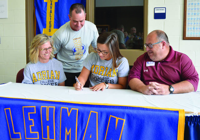 Molly Safreed, third from left signs her letter of intent to play soccer for Adrian College on Wednesday at Lehman Catholic. Watching are left to right mother Melissa Safreed, coach Jeremy Lorenzo and father Mark Safree.