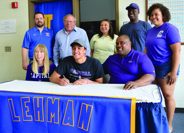 Kameron Lee, center front, signs his letter of intent to play football for Capital University on Wednesday at Lehman Catholic. Sitting with him are his mother, Peg Kameron, left, and dad, Kris Kameron. Standing are, left to right, football coaches Kent Witt and Dick Roll, Kirstyn Lee, Darien Wilkerson and Kassie Lee.