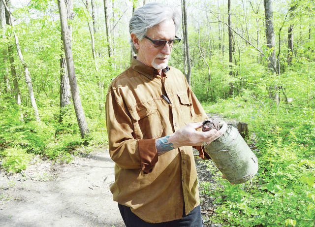 Neil Allen, of Sidney, takes a toy out of a geocache in Tawawa Park, Tuesday, May 8. He'll lead a geocaching expedition during the park's 70th anniversary celebration, June 30.