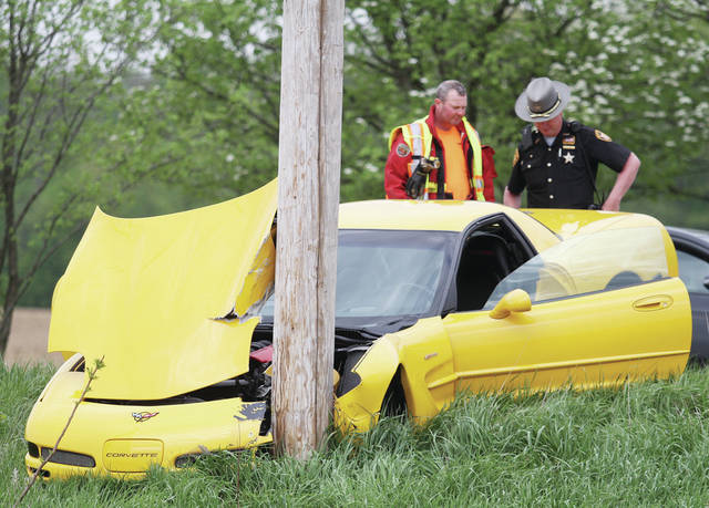 Investigators check damages after a Corvette crashed into a utility pole along county Road 65 near Port Jefferson, Saturday, May 12.
