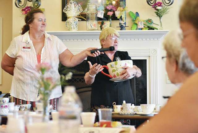 Kathy Gengler, right, of Delphos, talks about her tea cup collection, while Elmwood program coordinator Marge Luedeke, of New Bremen, holds a microphone for her. Gengler was one of the presenters at a Mother's Day program at Elmwood Assisted Living in New Bremen, May 11. Gengler talked about how different tea cups in her collection remind her of different kinds of people in the world and lessons from the Bible.