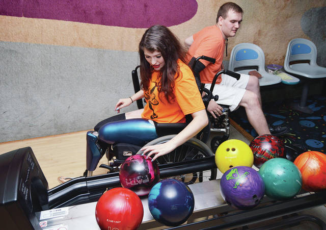Rachelle Cooper, left, and Kegan Latimer, both of Sidney, compete in some wheelchair bowling at Bel-Mar Lanes Saturday, May 12 during a benefit for Cooper who lost her legs while checking on a friend who had just hydroplaned into a railing when another car crashed into her friends car slamming its door on her legs. Cooper enjoys bowling and has continued to bowl from a wheelchair in a mixed double league. Cooper can now walk with high tech prosthetics. She plans on being able to bowl with her prosthetics in about a year. One of her prosthetics has a microprocessor in its knee that will be programmed to know how many steps she takes and when she bends to bowl. Cooper will be able to activate the knee with an application on her phone. Cooper's sister President of the Wright State gymnastics team Danielle Cooper brought the Wright State gymnastics team to bowl at the bowling benefit.
