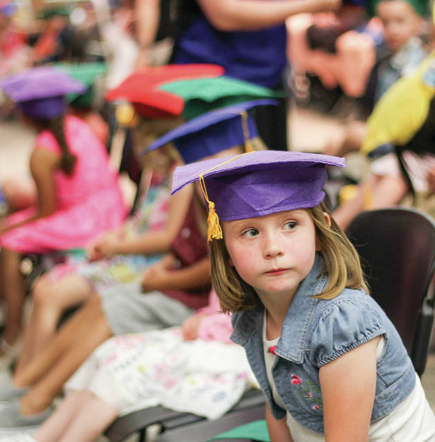 Lydia Slife, 4 , of Sidney, daughter of Crystal Slife patiently waits for her Shelby Hills preschool graduation to start at Sidney Middle School Thursday, May 17.