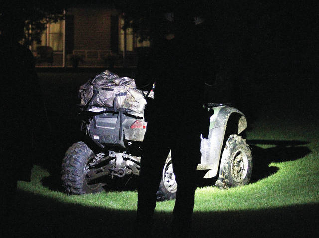 A Shelby County Sheriff's Deputy inspects the ATV that continued running into a field after a man was thrown from it.