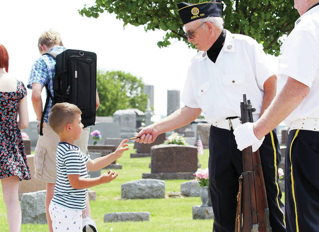 Anna American Legion member and Army Vet Gary Carr, right, of Anna, hands a spent shell casing to Wesley Thurman, 4, of Conover, son of Wes and Jenn Thurman, after a Memorial Day ceremony at Pearl Cemetery south of Anna Monday, May 28.
