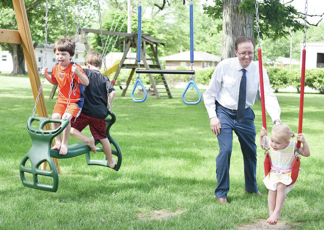 Michael Mayer, third from left, pushes his daughter, Frankie Mayer, 3, on a swing as his sons Elliot Mayer, 5, left, and Max Mayer, 8, in the backyard of their Russia home, Tuesday, May 29.
