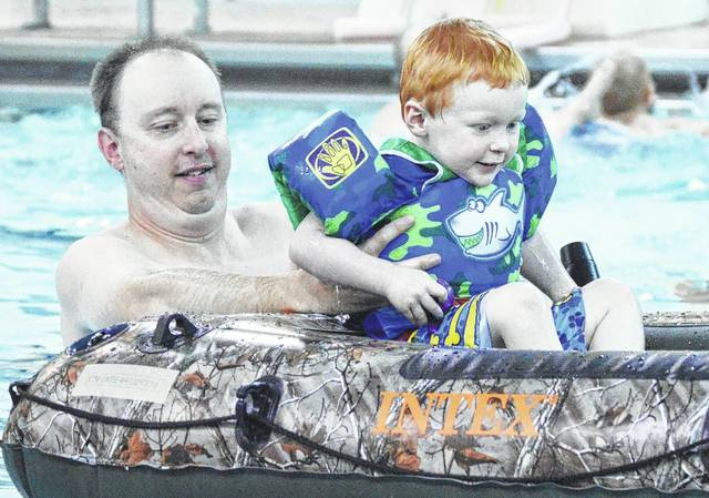 Jeff Bradley, left, places his son Damon Bradley, both of Sidney, son of Dr. Rosy McCarthy, into an inflatable raft during a 2017 Splash class at the Sidney-Shelby County YMCA. The raft is used to help teach kids to get into the habit of asking for permission to enter the water with a lifejacket on before getting into a boat. This year's Water Safety or Splash class will be held June 4-7.