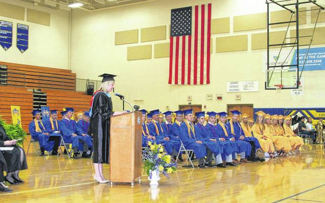 Lehman Catholic High School senior guidance counselor Kate Schulze presents scholarships during Sunday's graduation ceremony.