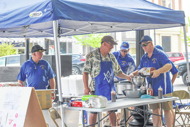 """Masonic Temperance Lodge 73 prepared barbecue dinners during Saturday's Farmers' Market. Working at the stand were, left to right, Nate Phillips, Sidney, Brian Huffman """"Road Dog BBQ,"""" Sidney, Michael Supinger, Russia, and Terry Cupp, Sidney."""