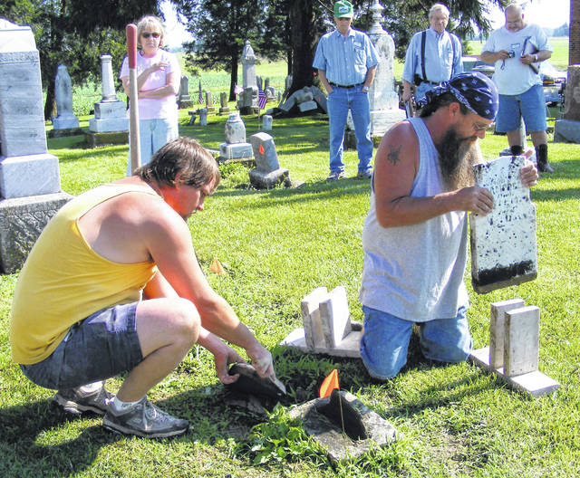 John Walters, right, and a member of his staff demonstrate tombstone repair at a previous event.