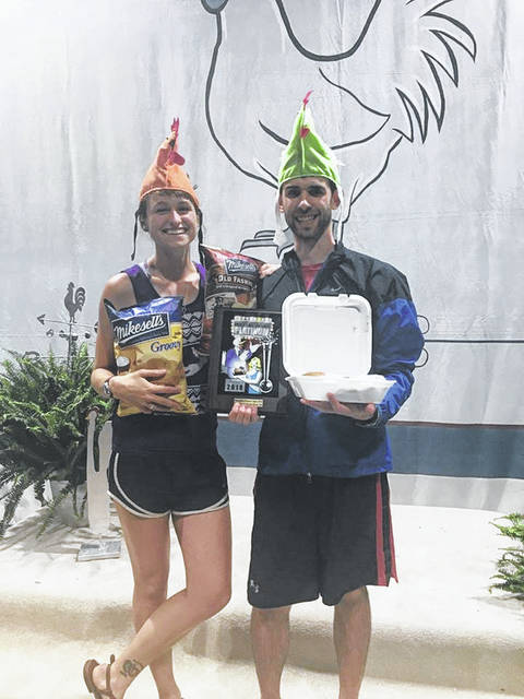 Ryan Stoneberger, of Columbus, and his fiancé, Alora Reiff, display the prizes he won for purchasing the 1,000,000 chicken dinner at Poultry Days Saturday.