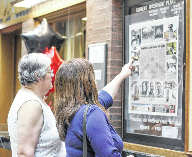 Barbara Searcy, of Sidney, and Karen Gates, of Russia, look at the display of a Sidney Daily News story about the 100th anniversary of Peoples Federal Savings and Loan Association, in the bank in Sidney, Thursday, May 31. The bank marked 100 years in its iconic Louis H. Sullivan-designed building with an open house that day.