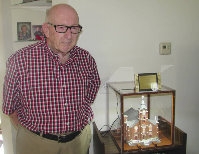 "Sam Wildow | Aim Media Midwest Charles ""Chuck"" Coby stands with his miniature replica of St. Mary's Catholic Church."