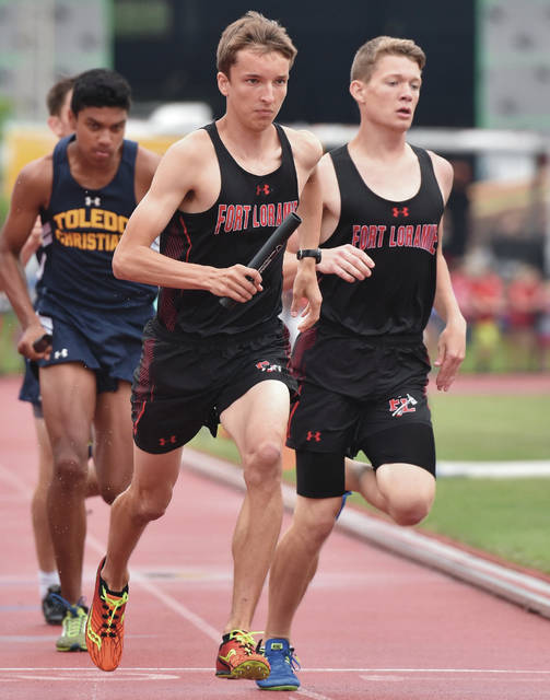 Fort Loramie's Jake Rethman runs with the baton after a hand off from Collin Luthman while competing in the 4x800 meter relay during the state track and field meet on Friday at Jesse Owens Stadium in Columbus.