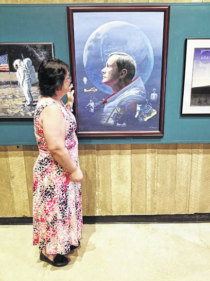 Deanna Kindell, of Sidney, admires a portrait of Neil Armstrong in the Armstrong Air & Space Museum in Wapakoneta, recently. Since January, Kindell has been the museum's development coordinator.