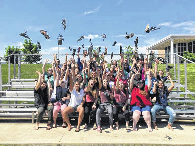 Jessica Witer, second from left in second row from the back, along with fellow missionaries, tosses her sandals in the air to celebrate the end of their training sessions with Experience Mission, in Fort Wayne, Indiana, recently. Witer, of Anna, is on a summer-long mission trip to Namibia, Africa.